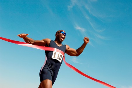 Picture of a athlete crossing the finish line with his arms in the air celebrating