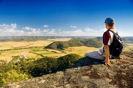 Picture of a man sitting on a ledge overlooking a wonderful green valley who has found his peace