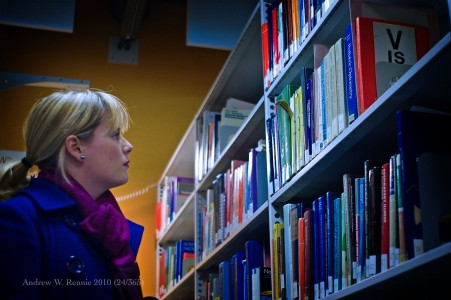 Picture of a woman searching the shelf for new books to read