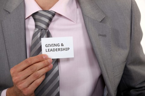 Picture of a leader holding a card saying Quotes & Leadership
