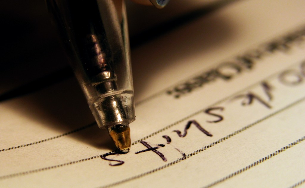 A Picture of a ball pint pen writing on lined paper