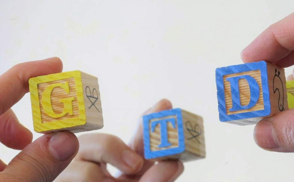 A Picture of three wooden blocks with letters 'G' 'T' 'D' on