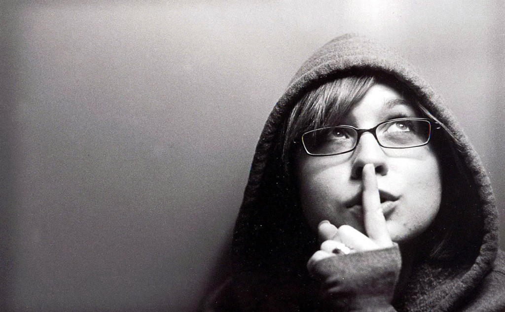 A Picture of a woman with her finger to her lips to say be quiet
