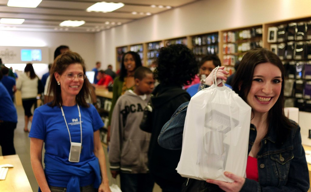 Happy Employee leaving Apple store with new iPad Air on Opening Day