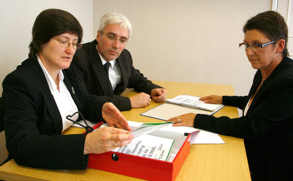 Group of 3 business people sitting at a table discussing information in some folders on the desk