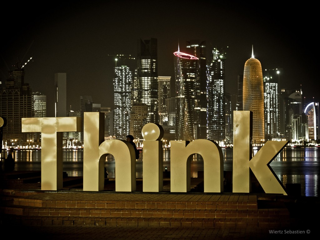 Picture of the word think infront of a major city that's lite up at night