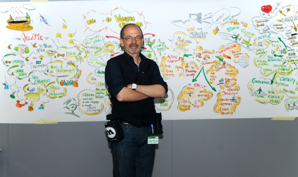 A Picture of a man who has created a highly detailed and colourful mindmap covering a white wall