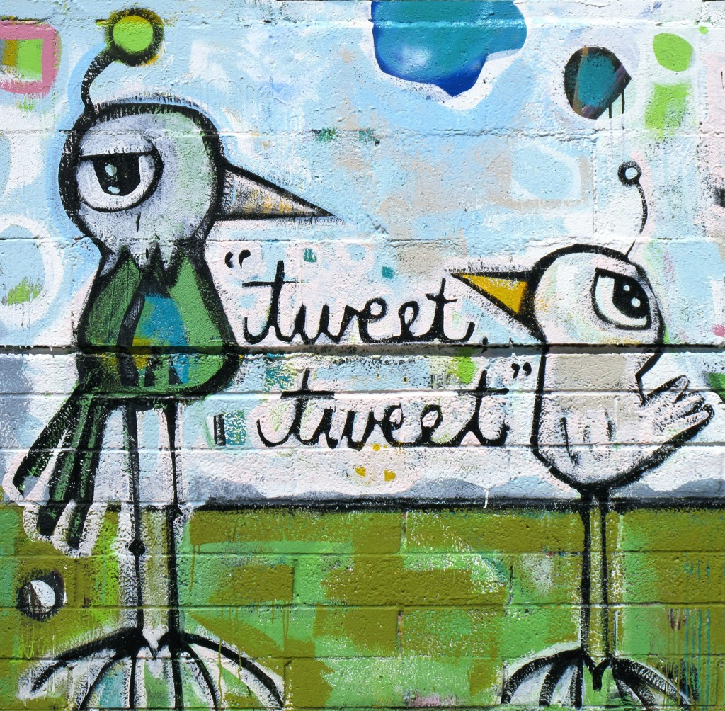 A Picture of a graffiti painting of two birds with the words 'Tweet Tweet' between them