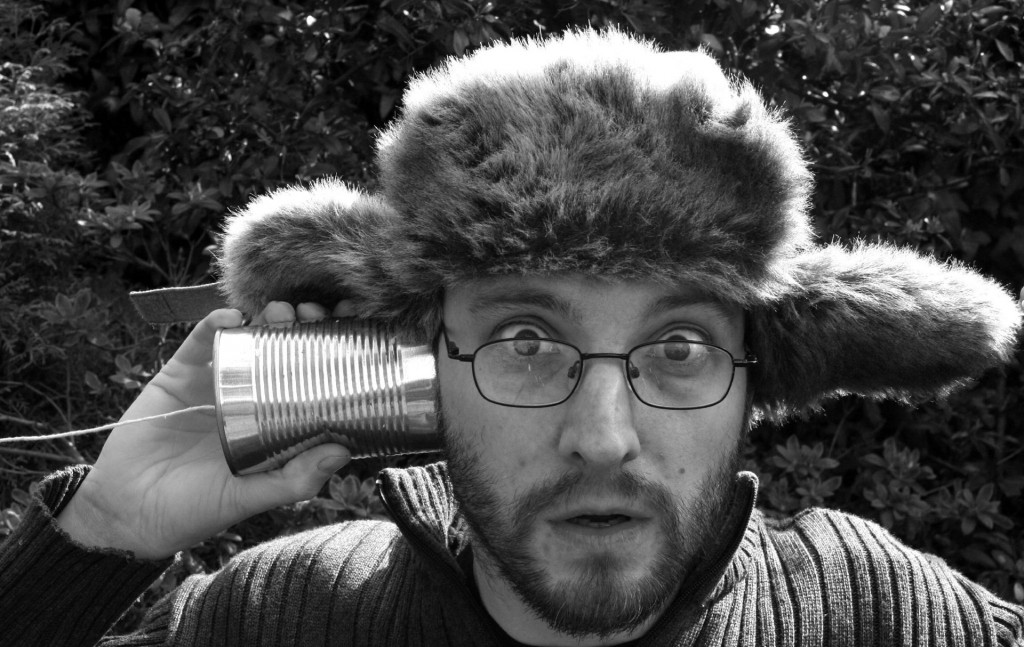 Picture of a man with a tin can connected to string to his ear