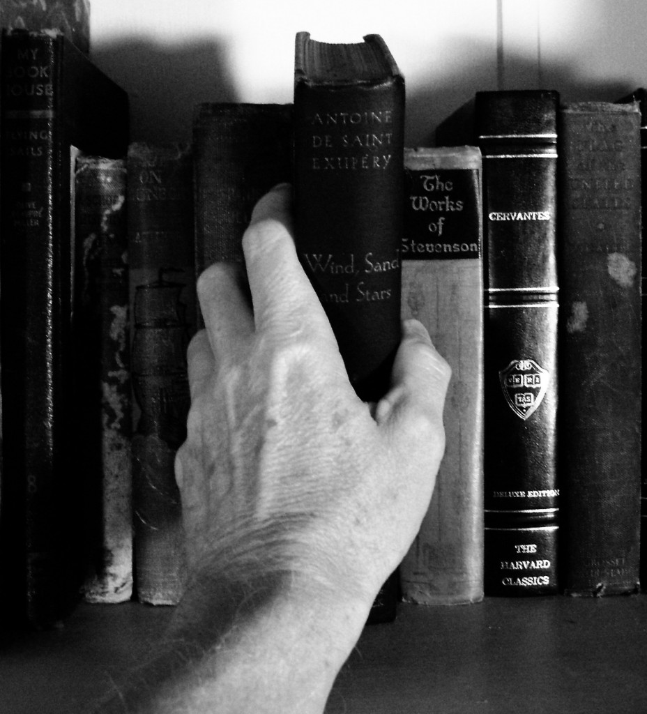 Picture of a persons hand picking a book from a bookcase