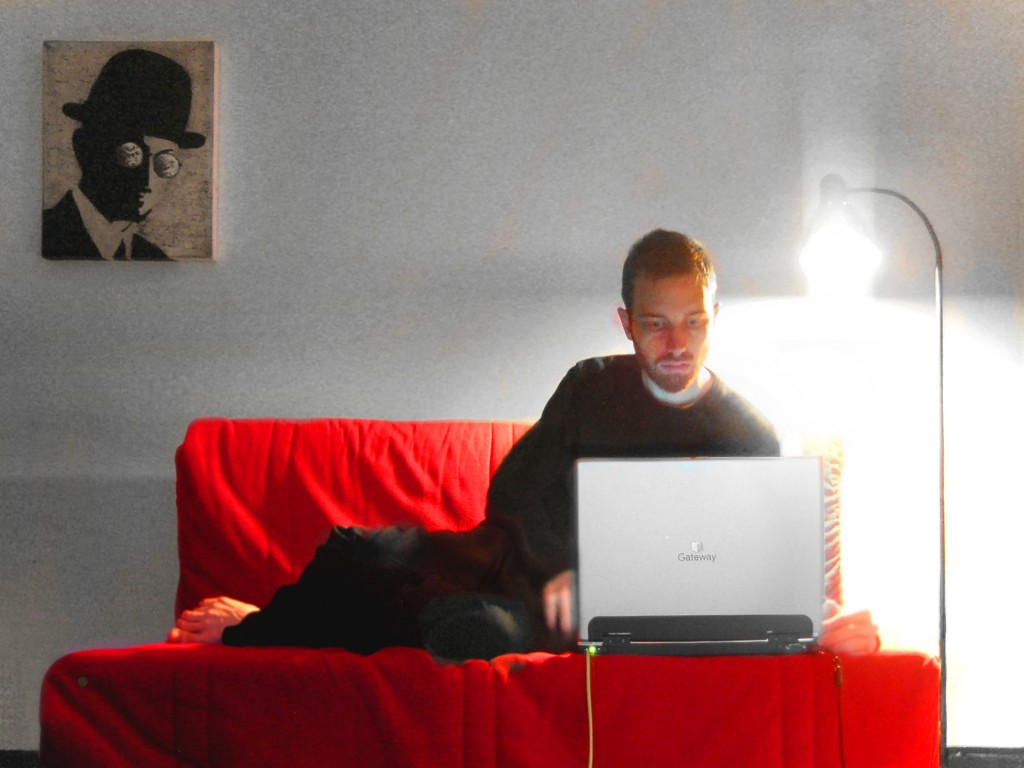 Picture of a man on a red sofa working on his computer