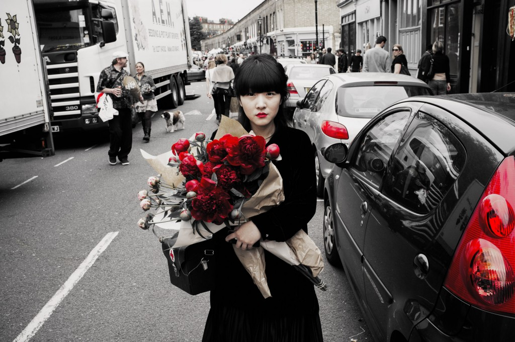 Picture of a woman in London street holding a bunch of red roses ready to give them to someone