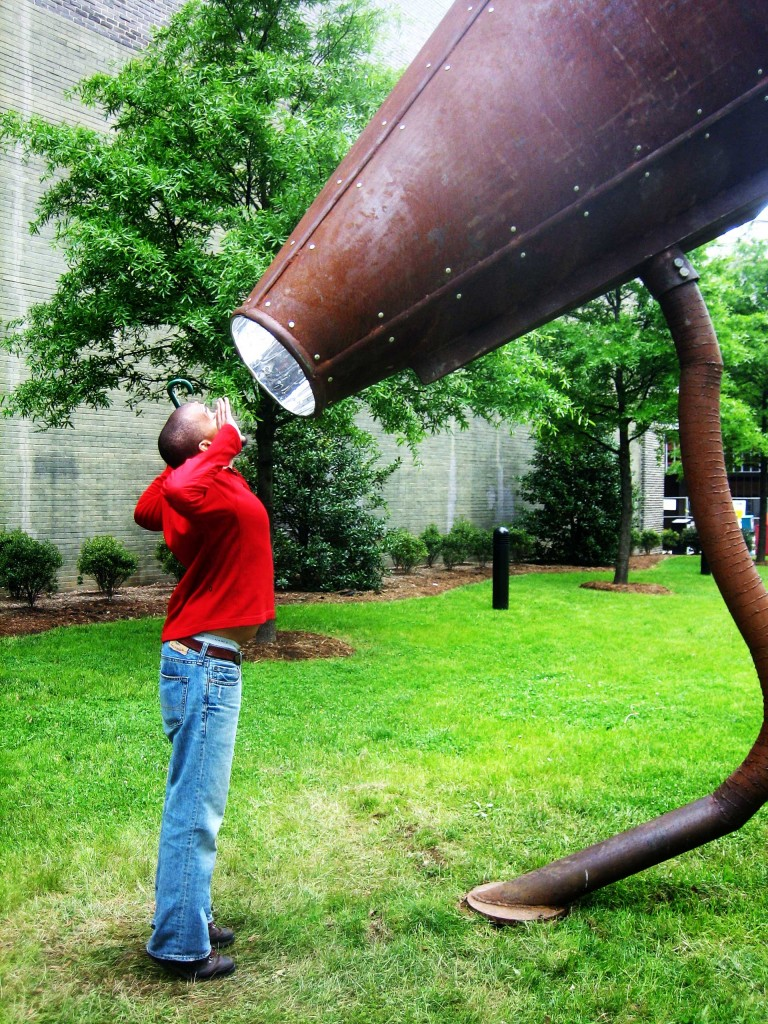 Picture of a boy shouting into a huge iron megaphone statue