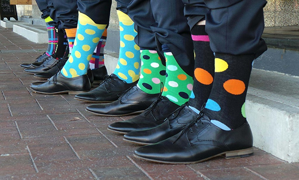 Picture of 4 people with multi coloured socks and business shoes on