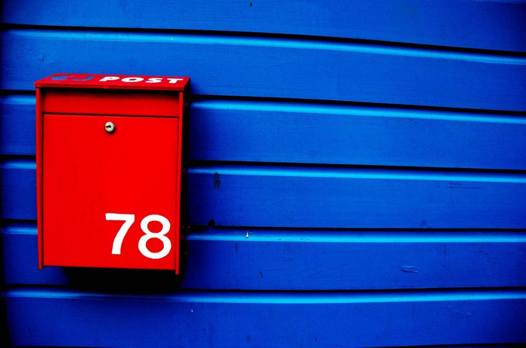 Picture of a red mailbox on a deep blue wooden gate