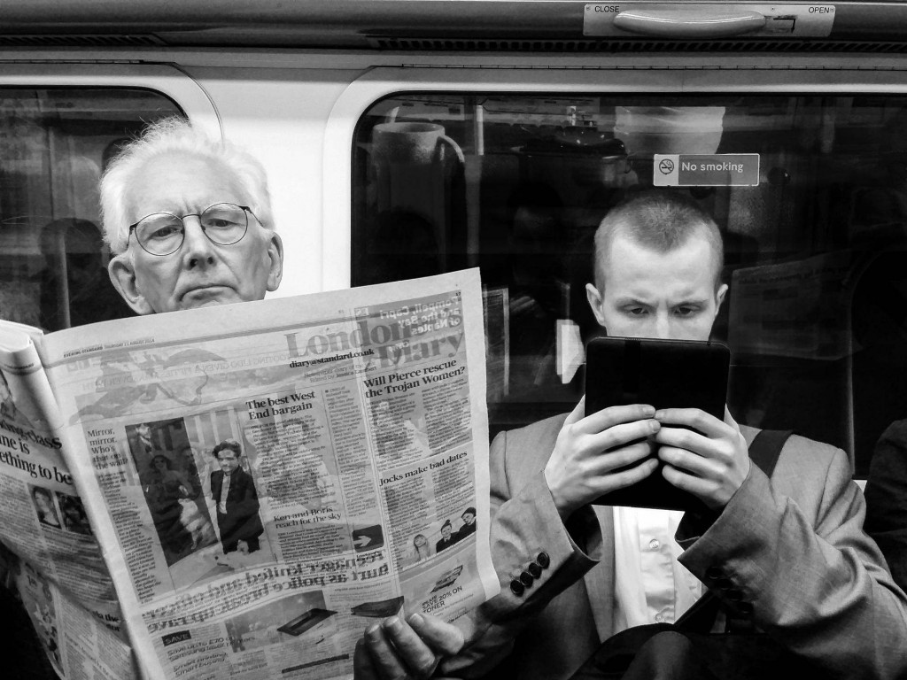 Picture of Man Reading Newspaper & Man Reading Electronic Device