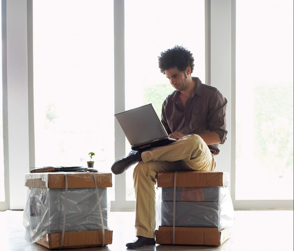 Picture of a man sitting on boxes looking at his laptop in a very nice modern looking office looking for small business startup grants 2015