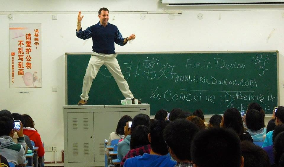 picture of Eric-Donlan the author of The Art Of Living In Joy standing on a lecture desk teaching some students