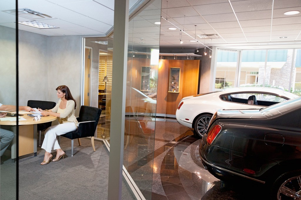 Picture of a woman signing the papers for new new car in a very nice Bentley dealership