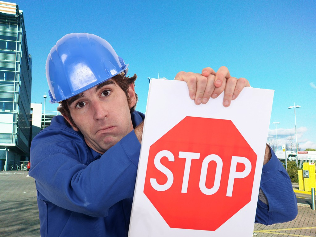 Picture of a man with a red stop sign on with a construction sight in the background