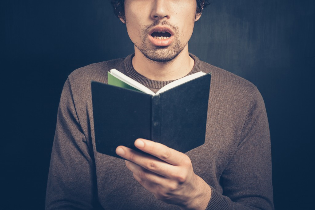 Picture of a man with a shocked face reading a book