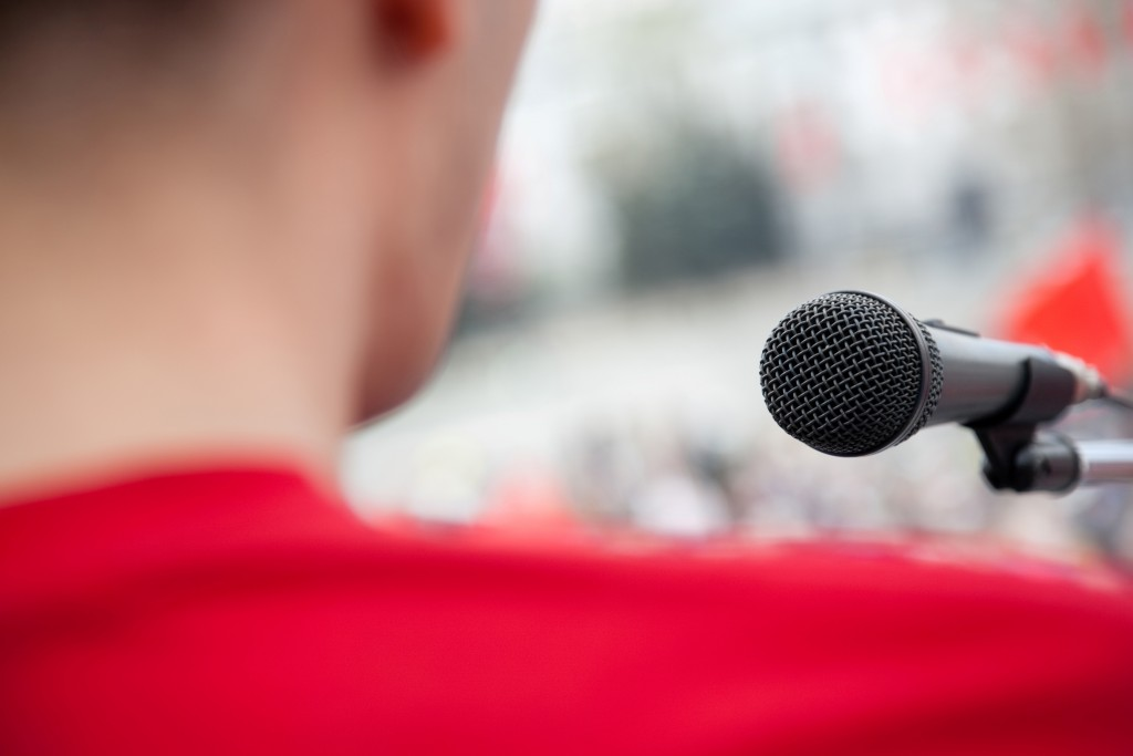 Picture from behind of a man standing by a microphone presenting