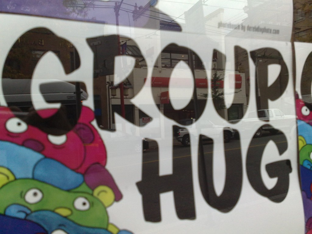 Picture of a sign in a shop that says Group Hug