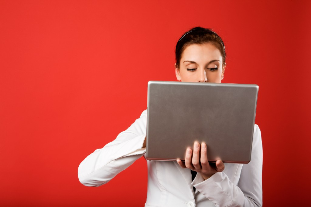 Picture of a woman holding a computer up near her face looking surprised with a bright red wall behind her.