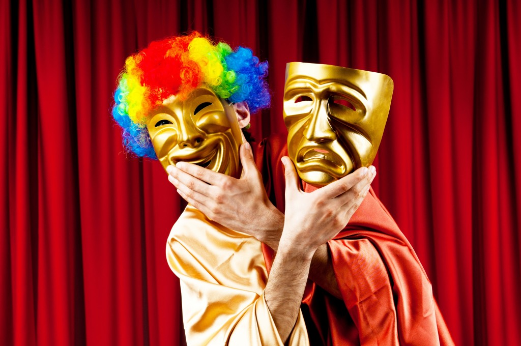 Picture of an actor with bright clown hair and holding a gold smiling mask to his face and another sad mask to the right of him