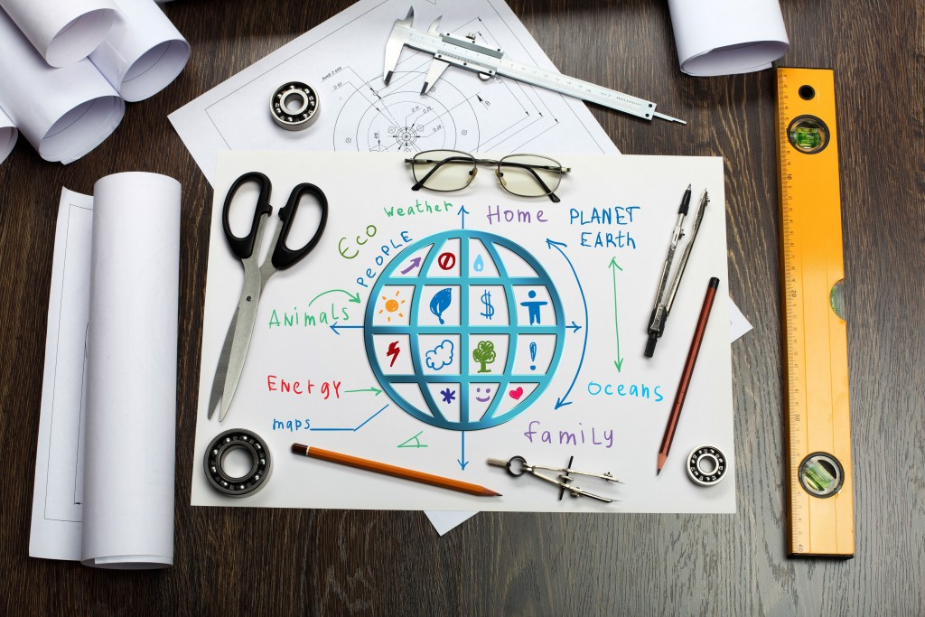 A Desk with scissors and pens on with some paper with a sketch of the world to show how to launch a sustainable (eco-friendly) business the right way