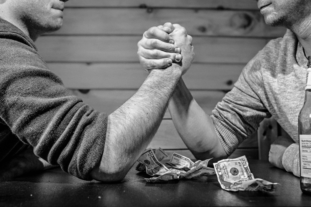 Budgeting 101 - Two men arm wrestling in a bar with a few dollars on the table.