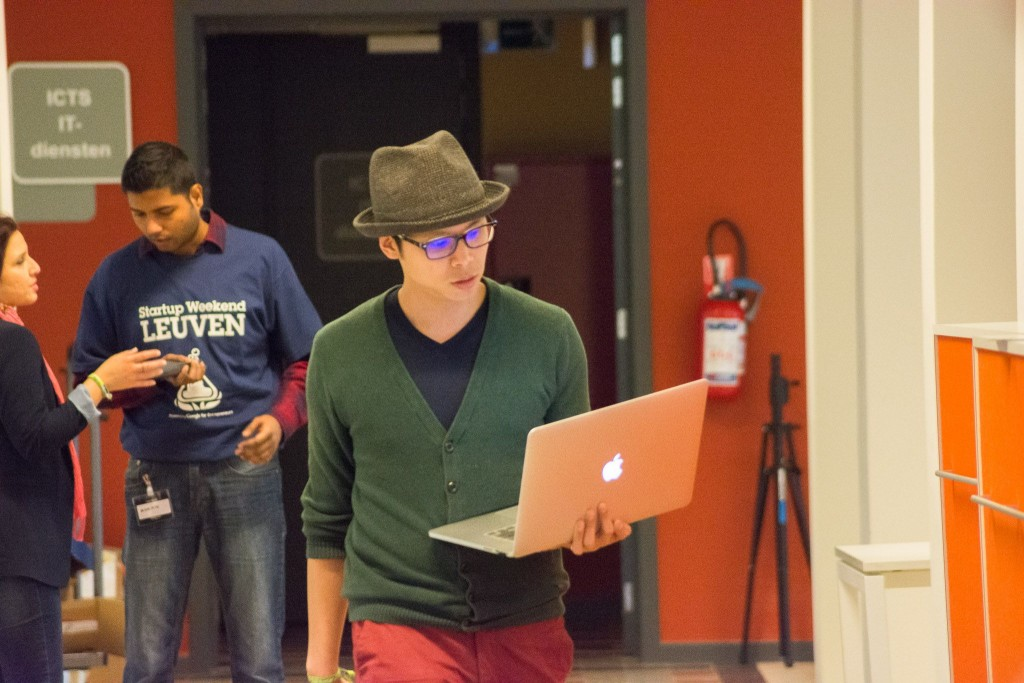 A Picture of a coder walking down a hall with a apple macbook