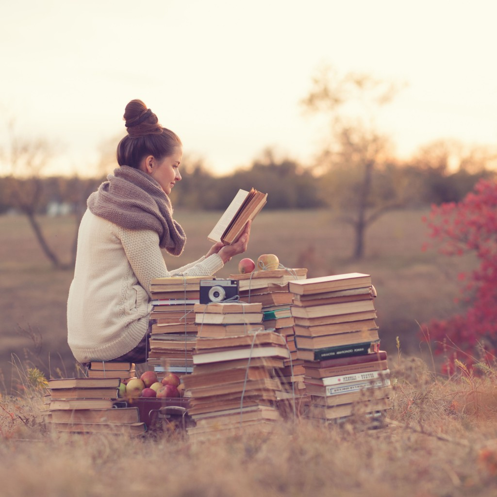 Picture of woman in the countryside with a stack of books reading the best StartUp Books of 2015